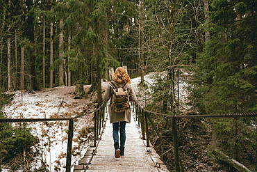 Redhead woman with backpack on footbridge in snowy woods