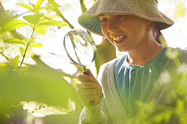 Smiling curious girl with magnifying glass examining plants