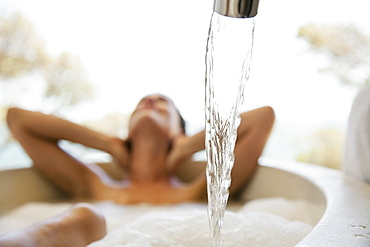 Sensual woman enjoying bubble bath behind water faucet