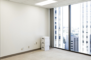 Boxes on floor in empty urban high-rise office