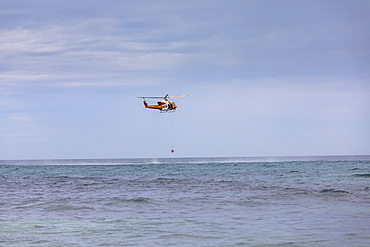 Rescue helicopter training over sunny ocean, Adelaide, Australia