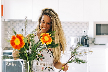Smiling young woman arranging flower bouquet in kitchen