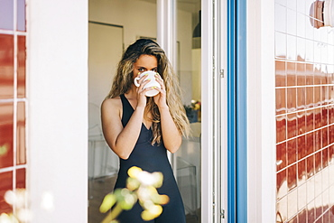 Portrait young woman drinking coffee in patio doorway