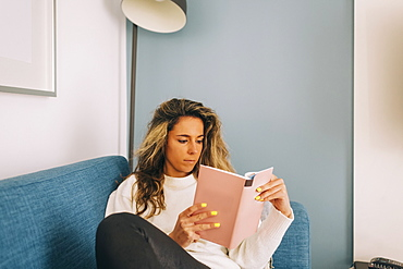 Young woman reading book on sofa