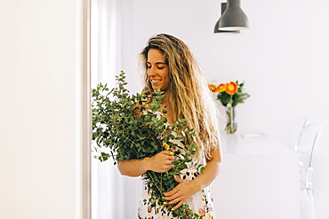 Smiling young woman holding bunch of fresh eucalyptus