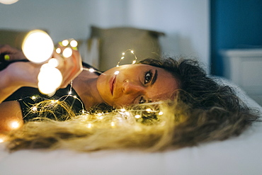 Portrait serene young woman with string lights on bed