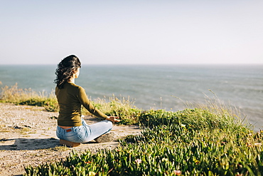 Serene woman meditating on sunny cliff overlooking sea