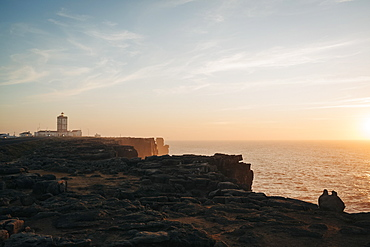 Scenic view lighthouse on cliffs overlooking tranquil seascape at sunset, Peniche, Portugal
