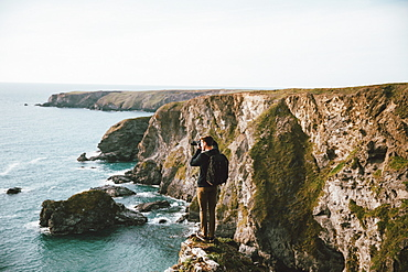 Male photographer on scenic ocean cliff, Bedruthan Steps, Cornwall, UK