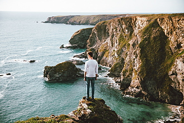Man standing at edge of cliff over scenic ocean, Bedruthan Steps, Cornwall, UK