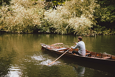 Man rowing canoe on tranquil River Avon, Bath, Somerset, UK