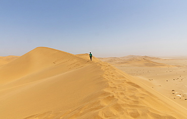Boy walking along sunny desert sand dune ridge, Namibia