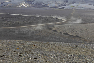 Dust cloud following car on dirt road in remote volcanic landscape, Iceland