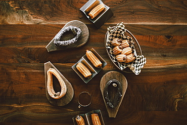 Overhead view variety of churros on wood table