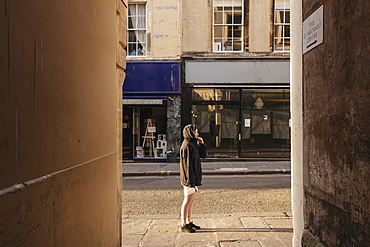Young woman in hoody standing on sunny empty street, Bath, Somerset, UK