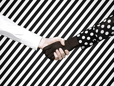 Multiethnic handshake on striped background