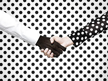 Multiethnic handshake on polka dot background