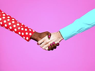 Multiethnic handshake on pink background