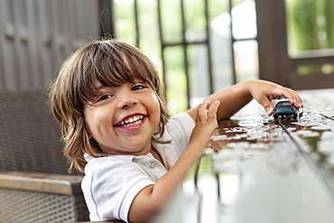 Portrait happy, cute toddler boy playing with toy car on wet patio table