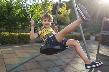 Portrait carefree boy swinging at sunny park playground