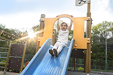 Portrait carefree girl on sunny playground slide