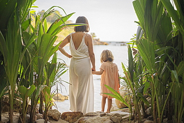 Mother and daughter holding hands on tropical beach, Thailand