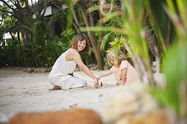 Portrait happy mother playing with daughter in sand on tropical beach