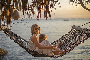 Portrait mother and daughter in hammock enjoying ocean sunset