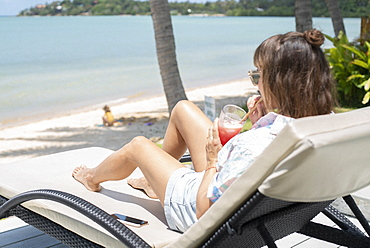 Woman drinking cocktail on sunny beach lounge chair