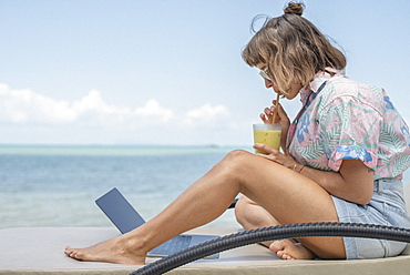 Woman sipping cocktail at laptop on beach lounge chair
