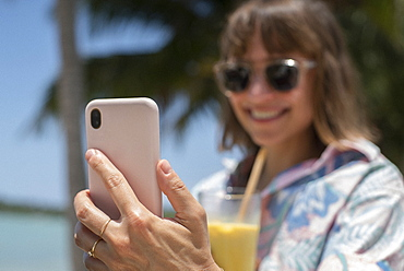 Happy woman with cocktail taking selfie on sunny beach