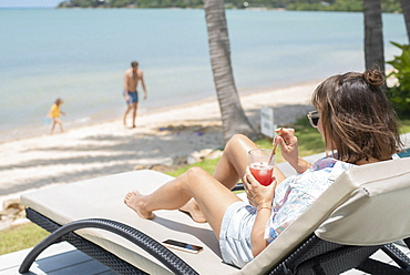 Woman enjoying cocktail on sunny beach lounge chair