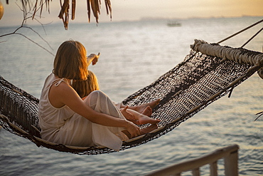 Mother and daughter in hammock enjoying ocean sunset