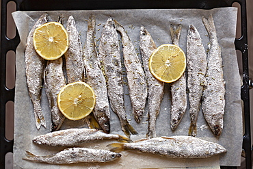 Fresh salted whole fish and lemon slices on parchment paper
