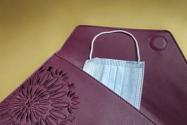 Disposable blue face mask in burgundy clutch purse