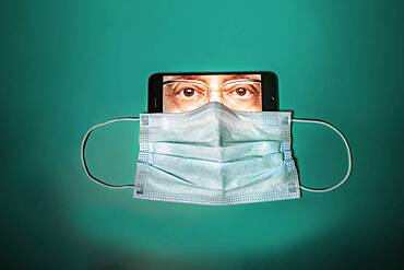 Face mask covering face of man on smart phone screen
