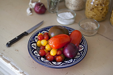 Various tomatoes with onion in plate