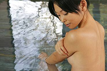 Beautiful nude young woman soaking in pool at spa