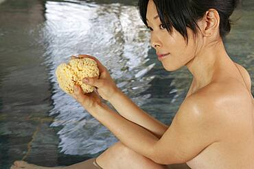 Beautiful young woman with loofah soaking in Onsen pool