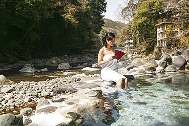 Young woman in towel reading book at sunny pool at Onsen, Izu, Japan