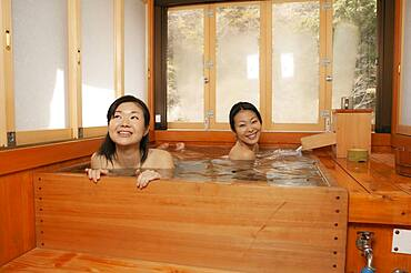 Happy young women friends soaking in wooden pool at Onsen