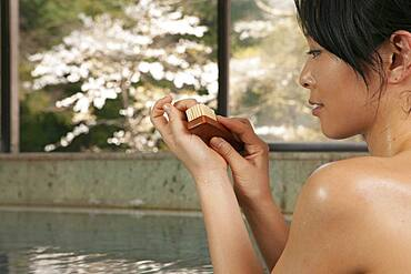 Young woman using nail brush in pool at Onsen
