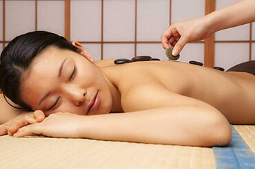 Tranquil young woman receiving hot stone massage at spa