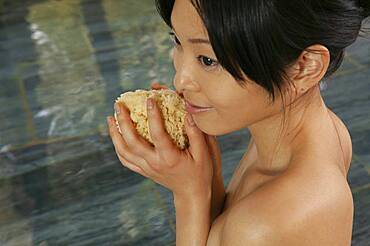 Beautiful young woman with loofah sponge in spa pool