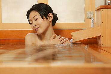 Serene young woman enjoying soak in pool at Onsen
