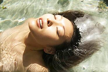 Close up beautiful serene young woman floating in sunny pool