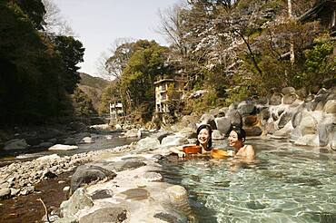 Happy young women soaking in sunny Onsen pool, Izu, Japan