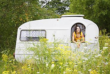 Happy young woman in camper trail in meadow