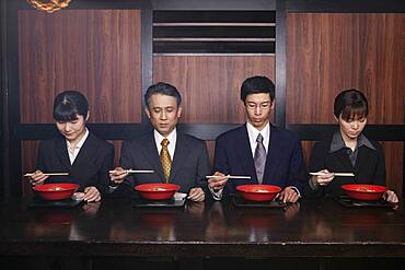 Japanese business people eating with chopsticks in restaurant