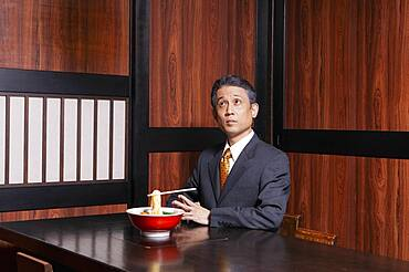 Businessman with levitating chopsticks and noodles in restaurant